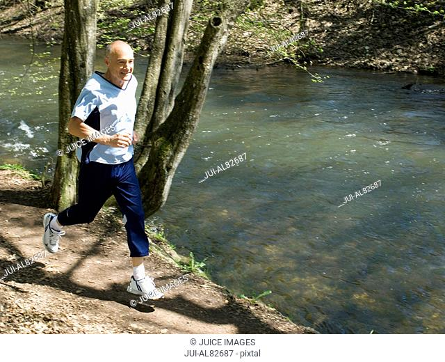 Senior man running on nature trail