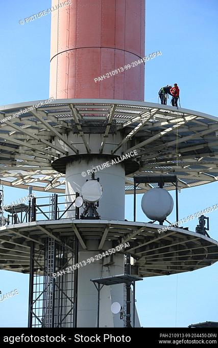 13 September 2021, Saxony-Anhalt, Schierke: Fitters stand on the transmission mast of the Brocken antenna. The specialists work on the antenna platforms at...