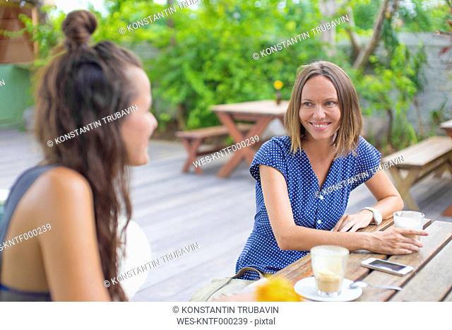 Two happy woman sitting at table talking