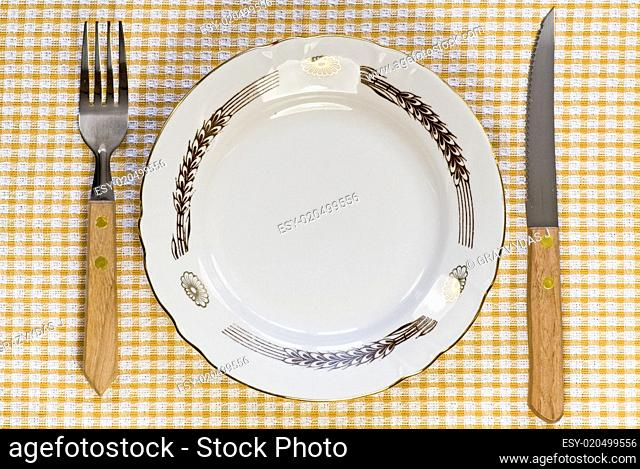 plate with fork and knife on tablecloth