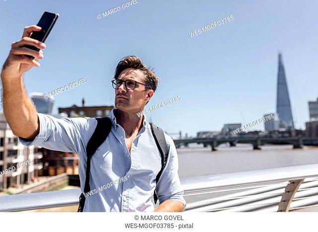 UK, London, man taking a selfie on Millennium Bridge