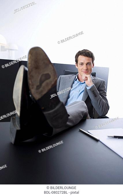 portrait of young entrepreneur sitting with his feet on desk