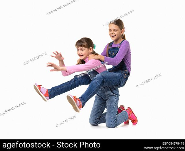Hilarious girl rides on herself riding her sister on a white background