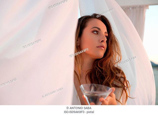 Young woman with cocktail glass in beach gazebo, Castiadas, Sardinia, Italy