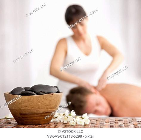 Man receiving massage, stones in bowl in foreground