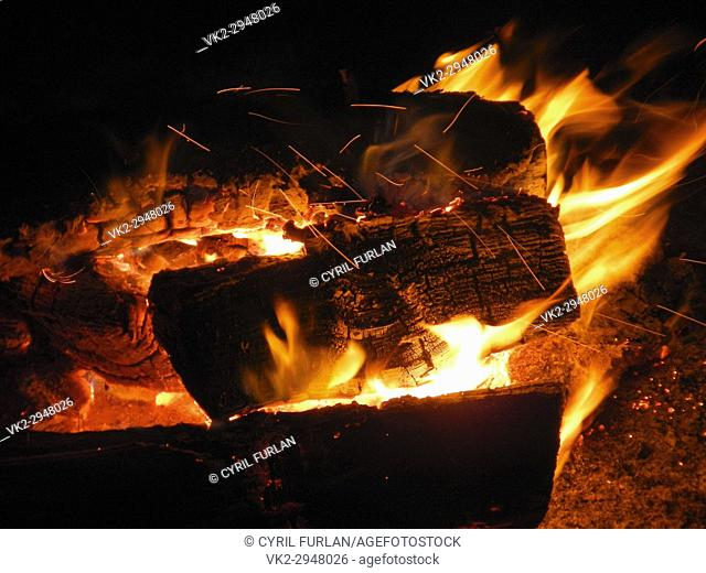 Hot burning campfire with hot coals, and sparks blown by he wind