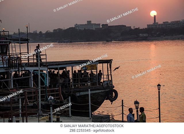 A ferry on the river Ganges (Hooghly) with the backdrop of the setting sun in Kolkata (Calcutta), West Bengal, India