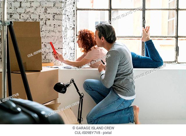 Couple moving into industrial style apartment, on window ledge looking at book