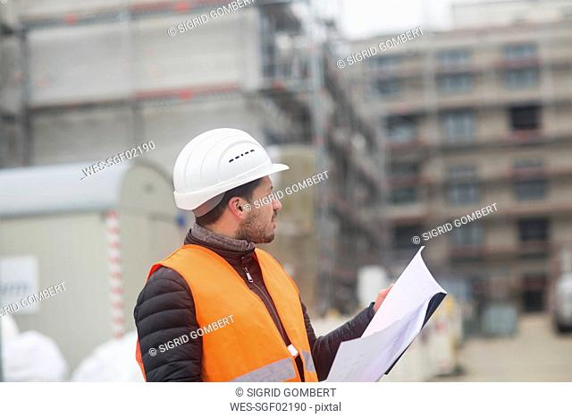 Man with plan wearing safety vest and hard hat at construction site