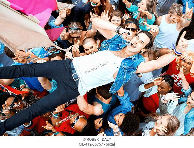 Performer singing and crowd surfing at music festival