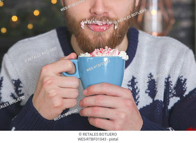 Man drinking hot chocolate with whipped cream and chopped candy canes at Christmas time