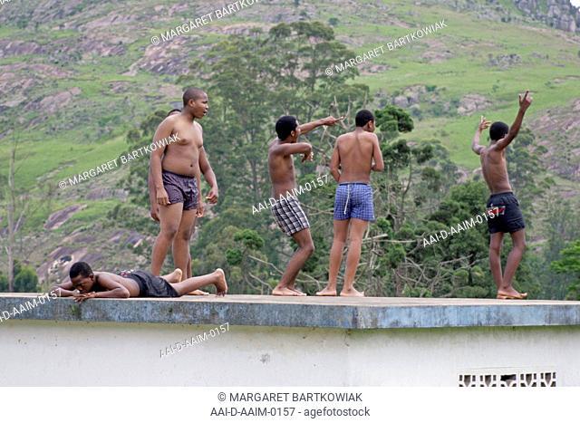 School boys standing on poolside rooftop, St Mark's School, Mbabane, Hhohho, Kingdom of Swaziland
