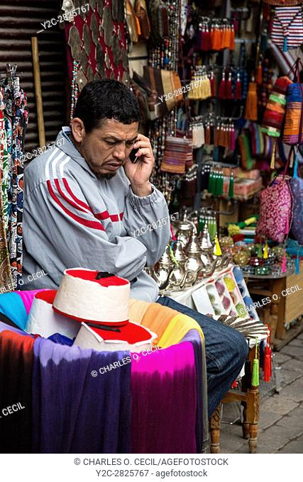Marrakesh, Morocco. Shop Vendor of Fezzes, Tea Pots, and Decorative Items Listening to his Cell Phone