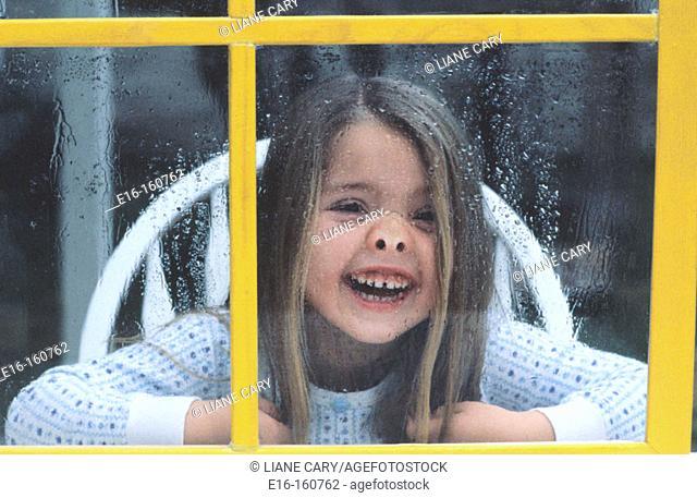 Girl behind yellow window
