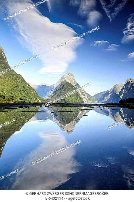 Mitre Peak with blue sky and clouds, reflection in the Milford Sound, Fiordland National Park, South Island, New Zealand