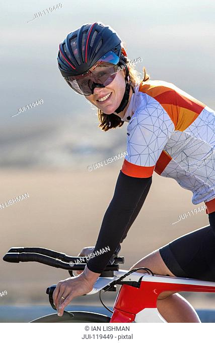 Close-up of female cyclist on race bicycle smiling at camera