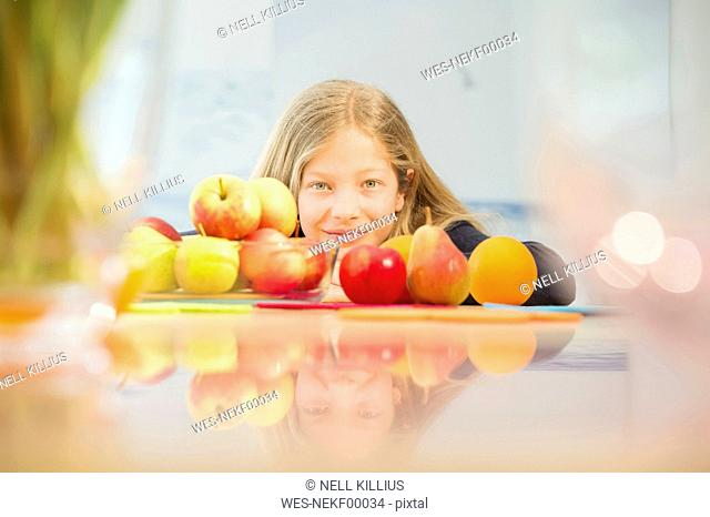 Portrait of smiling girl with various fruits