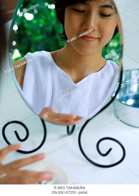 Reflection of a young woman in a hand mirror
