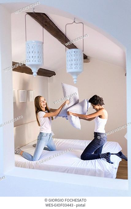 Playful female friends having a pillow fight in bed