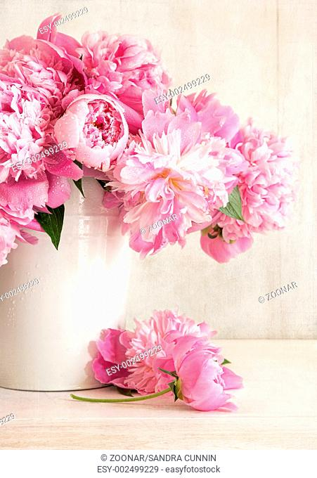 Pink peonies in vase on wood background