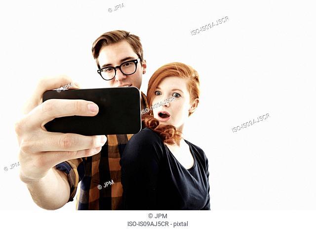 Studio shot of young couple posing for selfie on smartphone