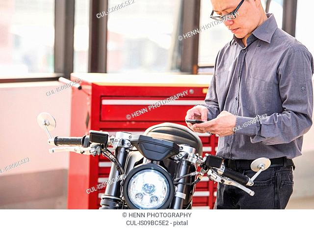 Man standing beside electric cafe racer motorbike, using smartphone