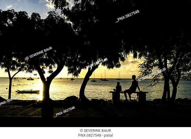 A father and his son sitted in front of the sunset, Saint-Louis, Marie-Galante, Guadeloupe, France