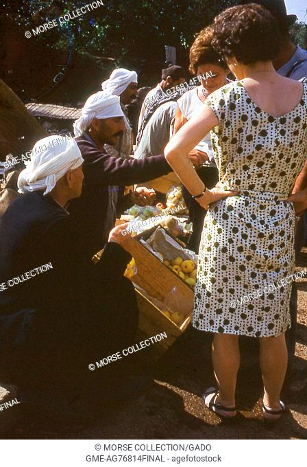 Western women shopping for apples from Druze merchants selling fruit by the roadway to Banias, Golan Heights, Israel, November, 1967