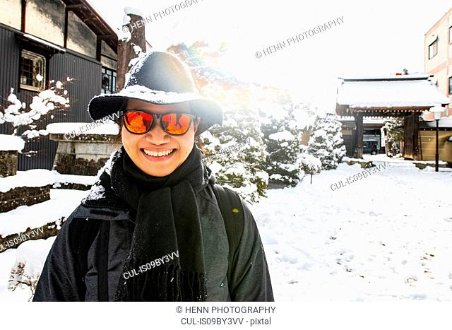 Woman in orange sunglasses and snow covered felt hat in winter, portrait, Takayama, Gifu, Japan