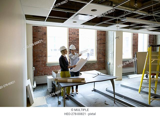 Architect and engineer discussing blueprints office construction site