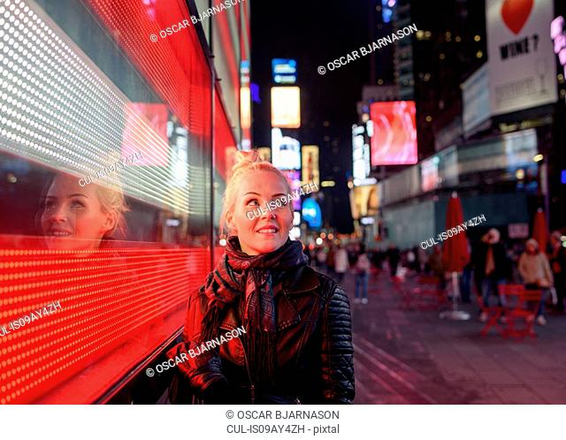Female tourist and Times Square led sign at night, New York, USA