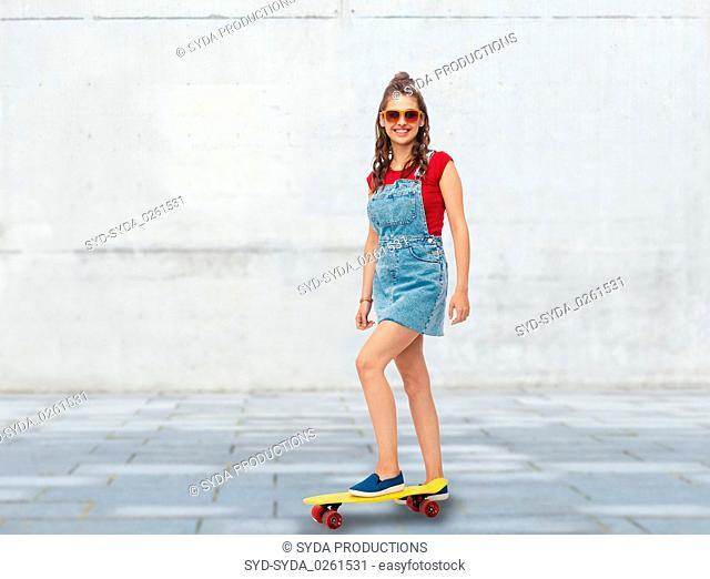 smiling teenage girl with skateboard on street