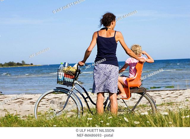 Mother and daughter with bicycle on beach