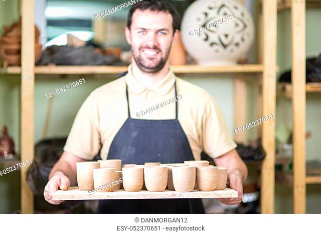 Portrait of Professional Male Ceramist Holding Wooden Tray with Clay Handmade Cups. Posing in Protective Apron in Workshop. Focus on Cups