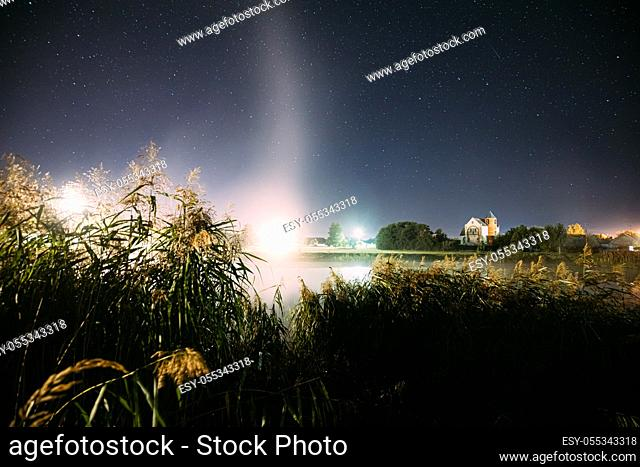 Evaporation Over River Lake Near Houses In Village. Night Starry Sky Above Misty Lake River Landscape At Night. Glowing Stars Above Summer Nature