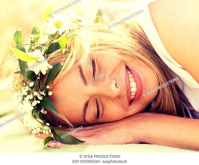 happy woman in wreath of flowers lying