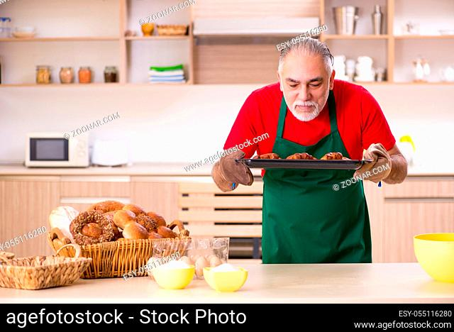 Old male baker working in the kitchen