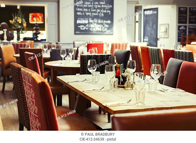 Wine glasses and silverware on table in empty restaurant