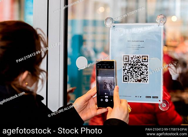 12 April 2021, Berlin: A woman scans a QR code at the entrance of a clothing store at Alexanderplatz to download the Luca app