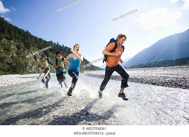 Germany, Bavaria, Tölzer Land, Young friends running through river