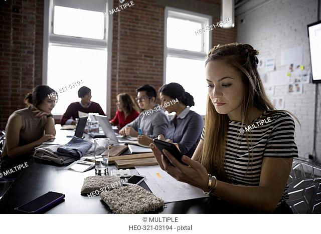 Female designer texting with cell phone in conference room meeting