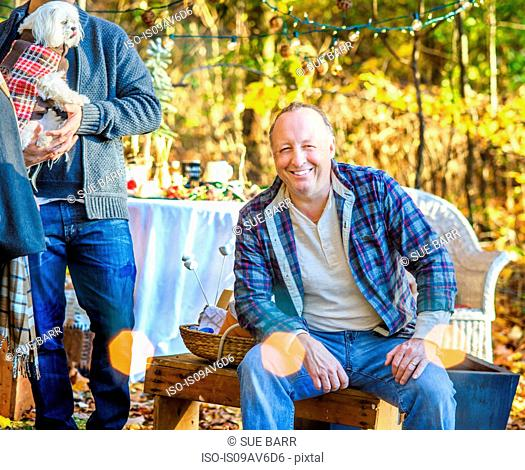 Portrait of mature man sitting in woods with adult son and dog