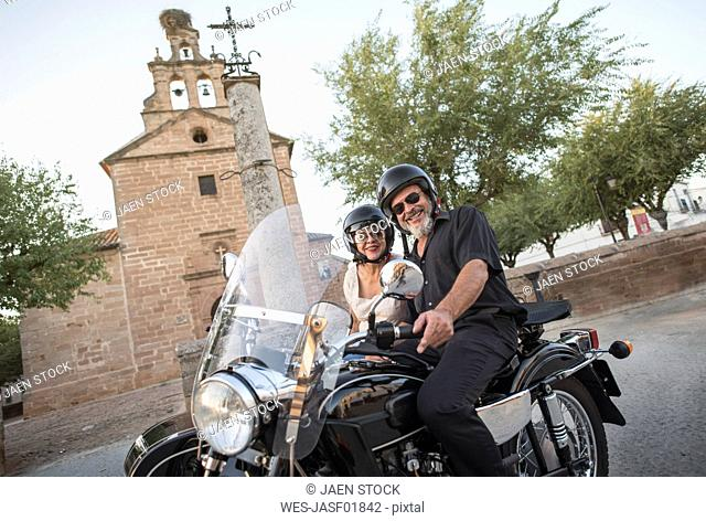 Spain, Banos de la Encina, mature couple with motorcycle with a sidecar at a church