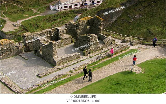 People walking by ruins of Tintagel Castle with fields and cliffs behind
