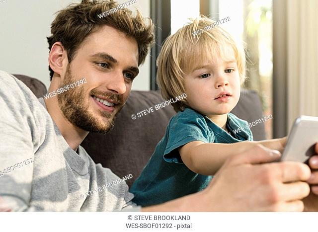 Father and son looking at smartphone on couch at home