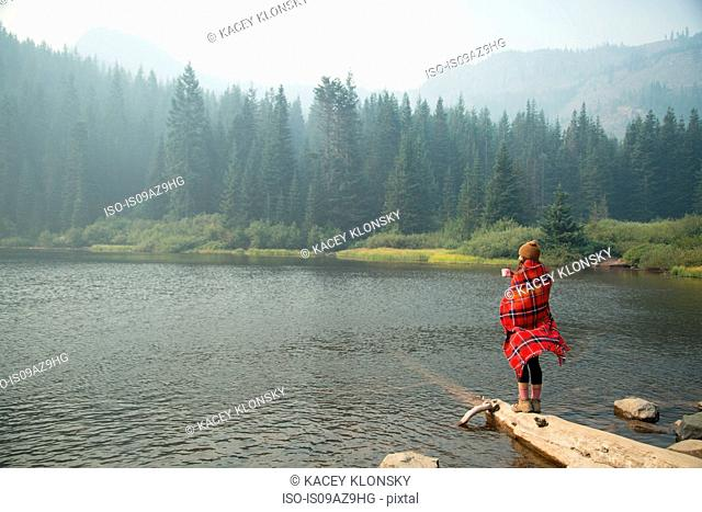 Woman wrapped in tartan blanket drinking coffee by misty lake, Mount Hood National Forest, Oregon, USA