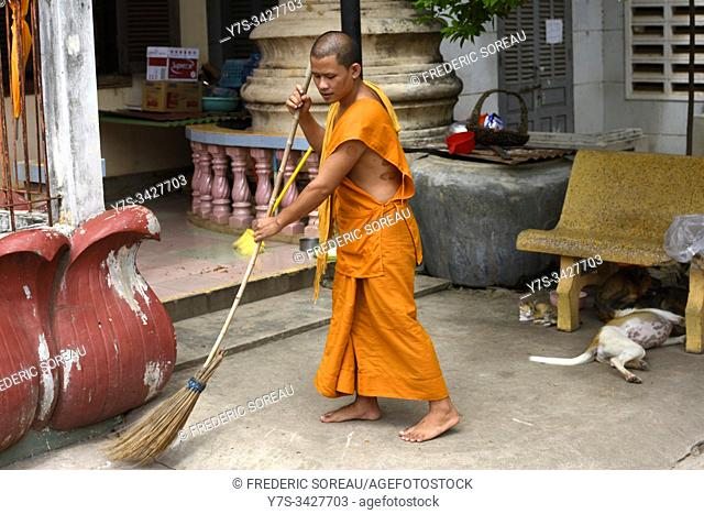 Buddhist monk sweeping grounds at dawn, Pagoda Preah Prom Rath,Wat Preah Prom Rath,Siem Reap,Cambodia,South Esat Asia