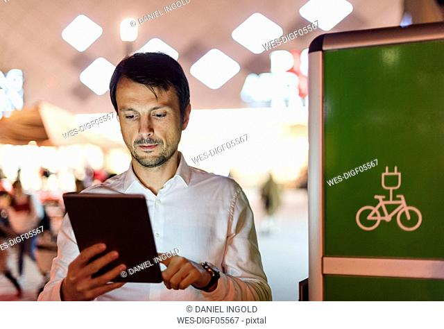 Businessman using digital tablet next to charging station