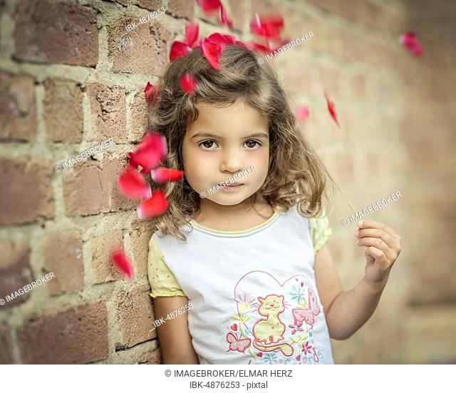 Girl, 3 years old, leans against a wall under flowers, Portrait, Germany, Europe