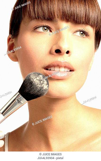Woman applying powder to face